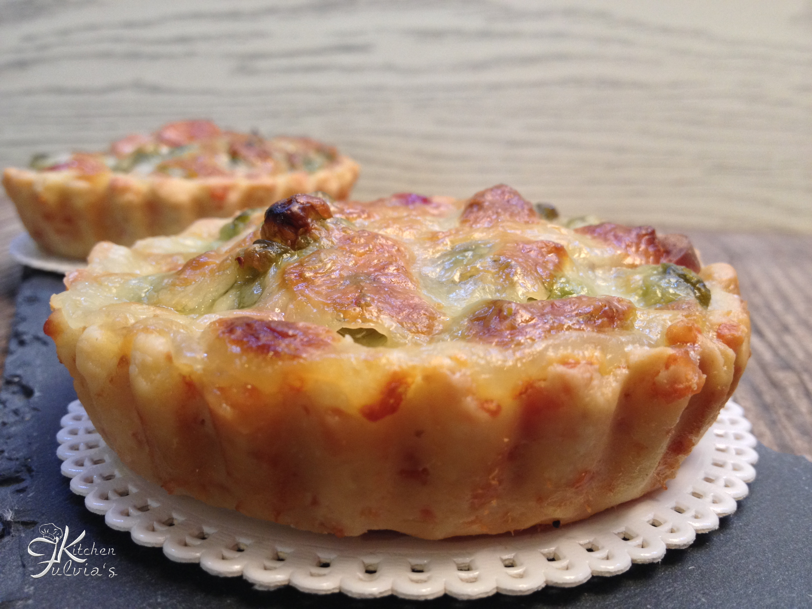 Mini quiche di frolla salata con piselli, wurstel e mozzarella
